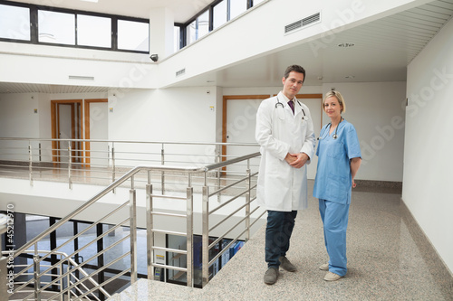 Nurse and doctor standing in hallway