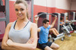 Smiling female trainer with arms crossed