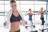 Woman smiling at front of aerobics class