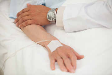 Doctor touching arm of elderly lady