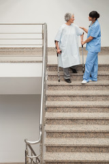 Elderly patient being helped by nurse to go down stairs