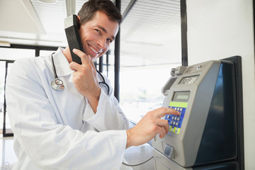 Smiling doctor phoning in the hospital