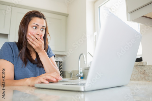 Woman shocked at laptop