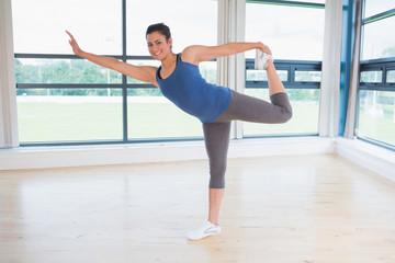 Smiling woman doing yoga pose