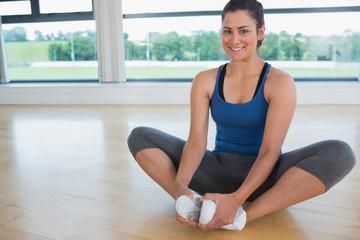 Smiling woman doing bound angle yoga pose