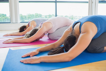 Women in childs pose in yoga class