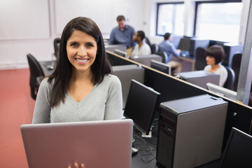 Woman using  laptop while others working at computers
