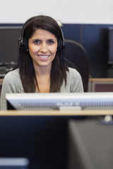 Smiling woman working in computer room