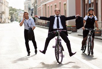 Businessmen and woman running and riding a bike