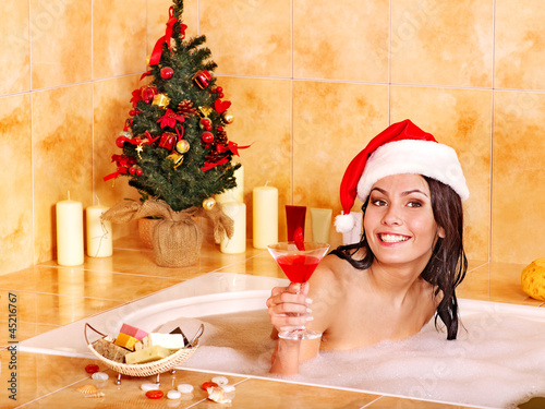 Woman in santa hat relax in bath.