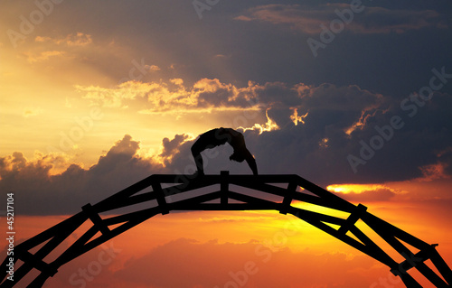 silhouette of gymnast on bridge in sunset