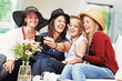 4 girls with straw hats and smartphone on the sofa