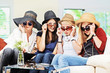 4 girls with straw hats and sunglasses on the sofa