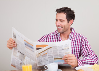 Young Man Reading Newspaper At Breakfast