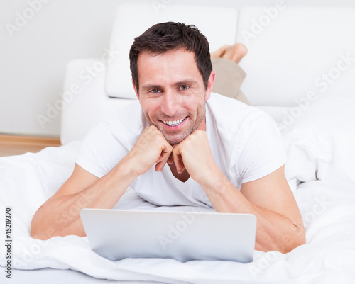 Portrait Of Young Man Lying On Bed Using Laptop