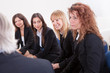 Businesswomen Looking At Mature Businessman