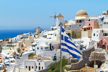 Oia village scenery with Greek flag on Santorini island