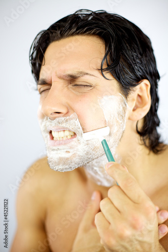 Young man hurting himself shaving with blade