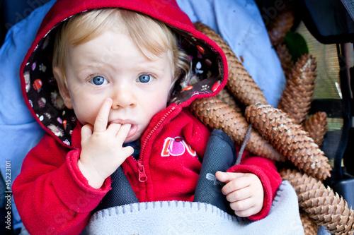 Herbstkind zwischen Tannenzapfen