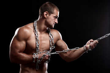 Handsome muscular guy with chains over his body