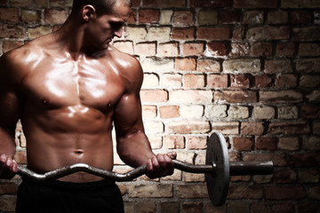 Young guy with muscular body with barbell