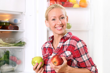 Happy woman is putting a food into the fridge