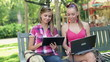 Happy students with laptop and tablet in the park