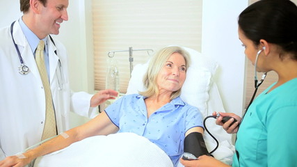 Hispanic Nurse Taking Patient Blood Pressure