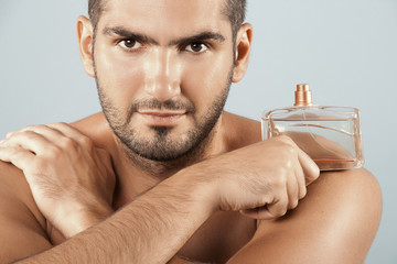 Closeup of cosmetics, Spa young man Holding fragrance