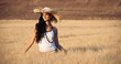 Young sexy woman in a wheat field with white dress and straw hat