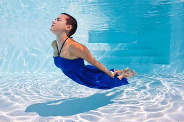 Underwater woman portrait with blue dress in swimming pool.