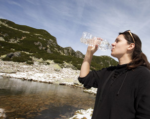 Woman drinking crystal clear water in mountain scenery