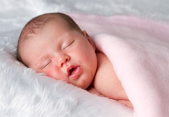 Sleeping newborn baby girl on tummy