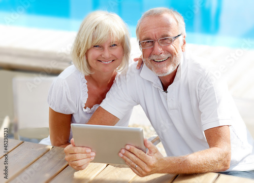 Different aged couple using a tablet pc outside - 45238733