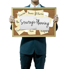 Business man holding board on the background, Strategic Planning