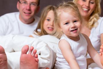 Gruppenbild einer jungen Familie im Bett