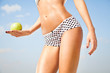 Woman perfect slim body holding an apple.