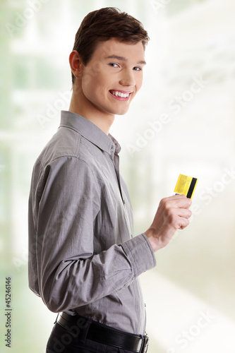 Young happy businessman holding credit card