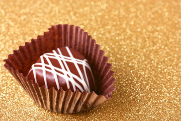 Chocolate candy on golden background