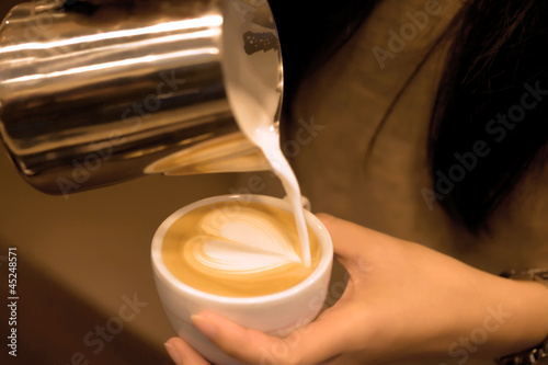 Hand pouring milk to do Latte art