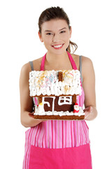 Young woman holding gingerbread house model