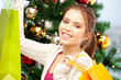 happy woman with shopping bags and christmas tree