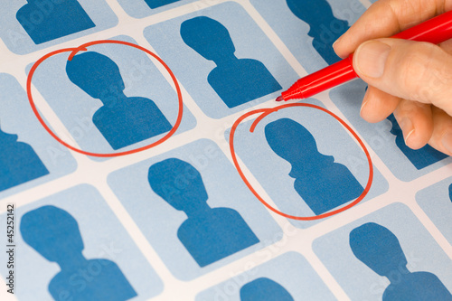 Hand Selecting Male and Female Candidates with Red Pen