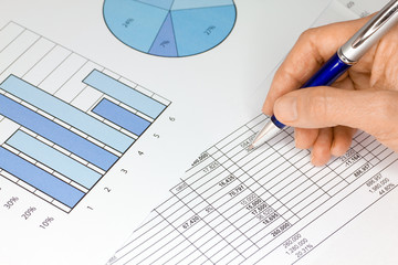 Hand with Pen Figures and Graphs in Blue