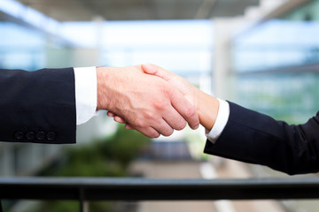 Man and woman shaking hands in office environment