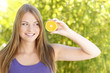 Hübsche Frau draußen mit Orangenscheibe