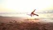 Jeune homme dansant sur la plage