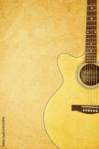 Color photo of an acoustic guitar near wall