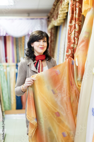 woman  chooses draperies