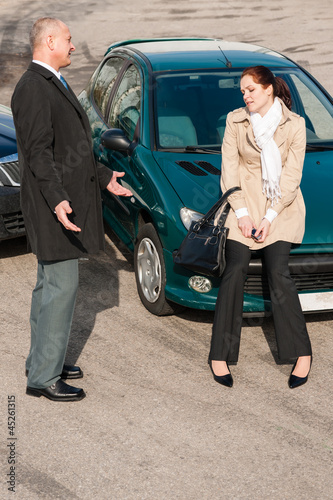 Man and woman talking after car crash